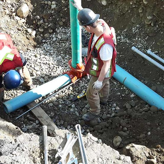 men measuring pipelines in underground site